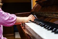 Liten flicka som studing för att spela pianot Arkivfoto