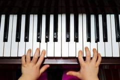 Liten flicka som studing för att spela pianot Fotografering för Bildbyråer