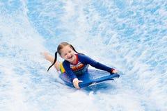 Liten flicka som surfar i strandvågsimulator arkivbild