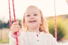 Liten flicka som svänger på en lekplats Barndom som är lycklig, utomhus- begrepp för sommar Royaltyfri Fotografi