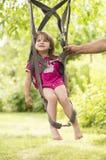 Liten flicka som svänger på remmar för en hoppa fallskärm Royaltyfria Bilder