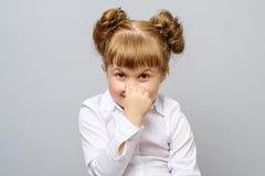 Liten flicka som täcker hennes näsa med hennes hand Royaltyfria Foton