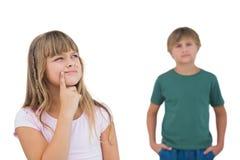 Liten flicka som tänker med pojken bak henne Arkivfoto