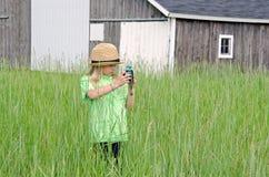 Liten flicka som tar ett foto med den gamla kameran arkivbilder