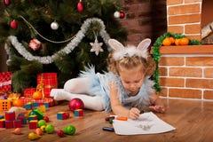Liten flicka som tecknar nära julgran royaltyfri bild