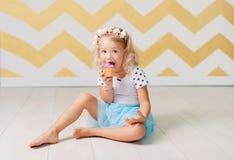 Liten flicka som äter caken Royaltyfria Bilder