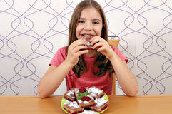 Liten flicka som äter den hemlagade pajen Royaltyfri Fotografi