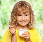 Liten flicka som äter yoghurt på sommar Royaltyfri Fotografi