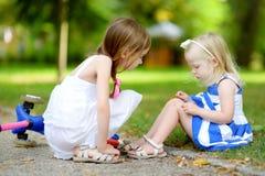 Liten flicka som tröstar hennes syster, efter hon har avverkat, medan rida hennes sparkcykel Arkivbild