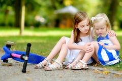 Liten flicka som tröstar hennes syster, efter hon har avverkat, medan rida hennes sparkcykel Fotografering för Bildbyråer