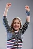Liten flicka som triumferar lyfta henne armar Royaltyfri Fotografi