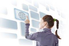 Liten flicka som trycker på en knapp av den faktiska skärmen med jordklotbild Fotografering för Bildbyråer