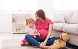 Liten flicka som trycker på hennes gravida moderbuk arkivbild
