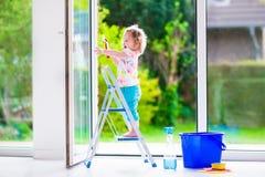 Liten flicka som tvättar ett fönster arkivfoto