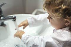Liten flicka som tvättar henne händer Royaltyfria Foton