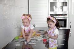 Liten flicka som två hemma förbereder kakor i kök fotografering för bildbyråer