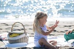 Liten flicka som tycker om en picknick på stranden Royaltyfria Foton