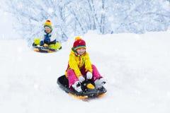 Liten flicka som tycker om en släderitt Sledding för barn Litet barnunge som rider en pulka Barnlek utomhus i snö Ungesläde i royaltyfri fotografi