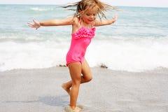 Liten flicka som tycker om på stranden Fotografering för Bildbyråer