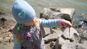 Liten flicka som undersöker en daggmask på fiske lager videofilmer