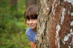 Liten flicka som ut bakifrån kikar en trädstam Royaltyfri Fotografi