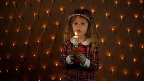 Liten flicka som ut blåser en stearinljus på en festlig kaka arkivfilmer