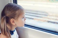 Liten flicka som ut ser fönstret av drevet Royaltyfria Foton