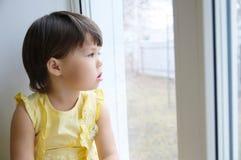 Liten flicka som ut ser fönstret som längtar efter något solsken barnsammanträdehem på den regniga dagen Arkivfoto