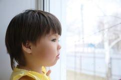 Liten flicka som ut ser fönstret som längtar efter något solsken barnsammanträdehem på den regniga dagen Royaltyfri Foto