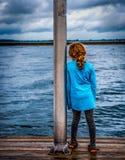 Liten flicka som ut ser till sjön Arkivfoto