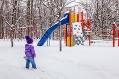 Liten flicka som utanför går Unge som ser den snöig barnlekplatsen Royaltyfri Foto