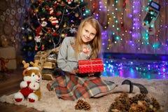Liten flicka som väntar på ett mirakel i julpynt Royaltyfri Bild