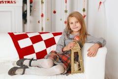 Liten flicka som väntar på ett mirakel i julpynt Fotografering för Bildbyråer