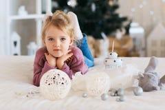 Liten flicka som väntar på ett mirakel i julpynt Royaltyfria Bilder
