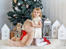 Liten flicka som väntar på ett mirakel i julpynt Arkivfoto