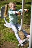 Liten flicka som övar på den utomhus- konditionmaskinen Arkivbild