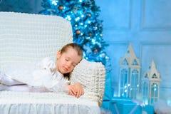 Liten flicka som vilar nära julgranen royaltyfri foto