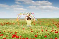 Liten flicka som vinkar med färgrika band på äng i vår royaltyfri fotografi