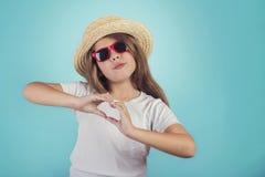 Liten flicka som visar hjärta med händer arkivfoto