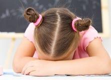 Liten flicka sovar på henne writing-boken arkivbild