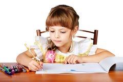Liten flicka tecknar i ett album arkivfoton
