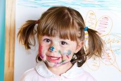 Liten flicka tecknar målarfärger arkivbild