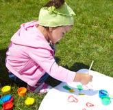 Liten flicka tecknar målarfärger arkivfoton