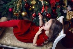 Liten flicka tre år i rött ligga för klänningläppstift Arkivfoton