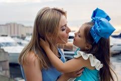 Liten flicka tre år som sitter på varven av modern med långt blont hår Royaltyfri Foto