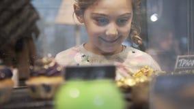 Liten flicka valda kaka och efterrätter Fönstret av kakan shoppar med variation av kakor på skärm lager videofilmer
