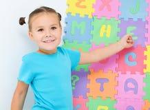 Liten flicka visar bokstav E på alfabetet arkivfoton