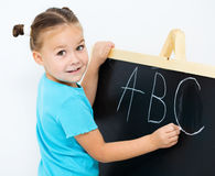 Liten flicka visar bokstav E på alfabetet royaltyfri foto
