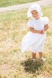 Liten flickaanseende i en sätta in i vitklänning Royaltyfria Bilder