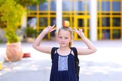 Liten flickaanseende med Apple på hennes huvud royaltyfri fotografi